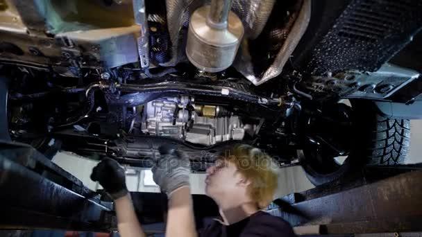 opravář autodílna stojící pod zdviženým automobil a zkoumání podrobností, kontrola vůlí v suspenzi