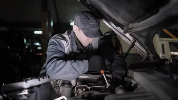 Profesionální auto servisního technika se snaží opravit vozidlo s pomocí klíč, on odšroubováním podrobnosti do kapuce