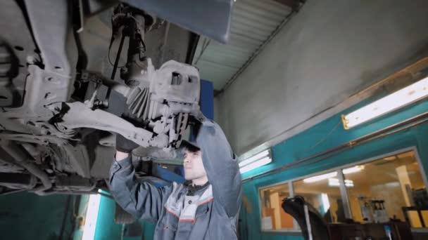 Profesionální opravář kontroluje ovladatelnost kola, aby auto opravit