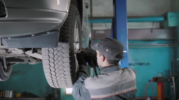 Car mechanic replacing wheel on car