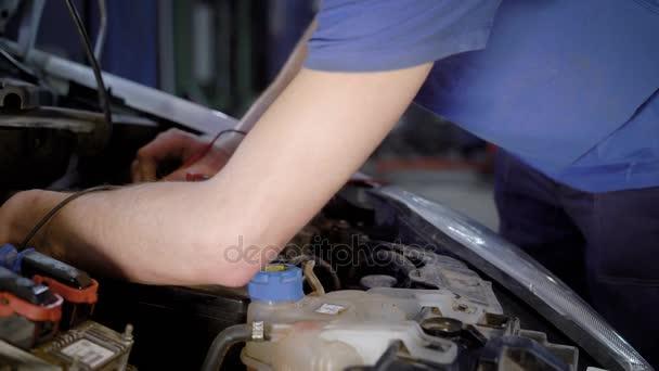 zblízka střílel z mechaniky ruce, kdo pracuje s otevřenou kapotou na vozidle, opravuje auto