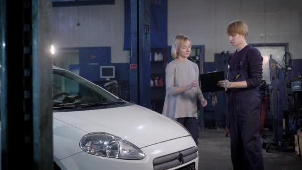 profesionální mechanik dává zákazníkovi auto, který byl opravárenské dílně, autě, si bere obraz