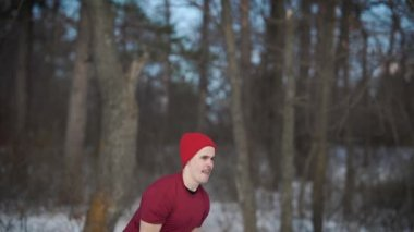 weightlifter is wearing red hat is rising and dropping a heavy kettlebell in a forest in winter day
