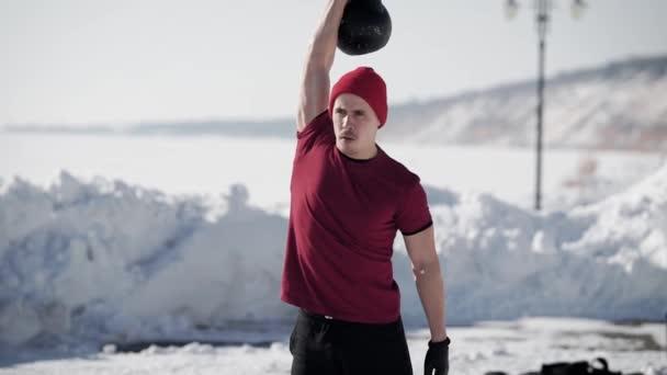 mladý pohledný muž je zvedání váhy jednou rukou stojící venku v zimě slunečný den v parku, zdravého životního stylu