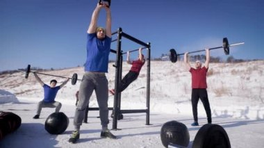 group of four young sportsmen are training on a sport area in winter day, one is pulling up on beam, second is lifting kettlebell, two are lifting rods