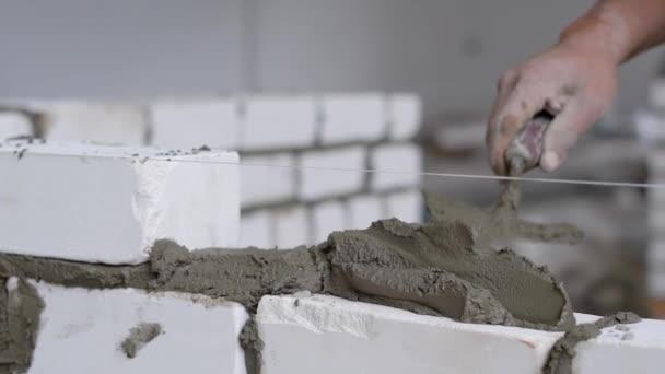 Detailní záběr záběr stavební dělník zdění bílé na zeď