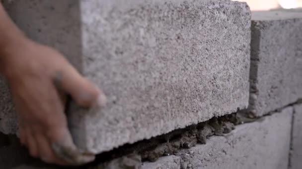 Detailní záběr záběr tvůrce pracující na místě a bulding zeď