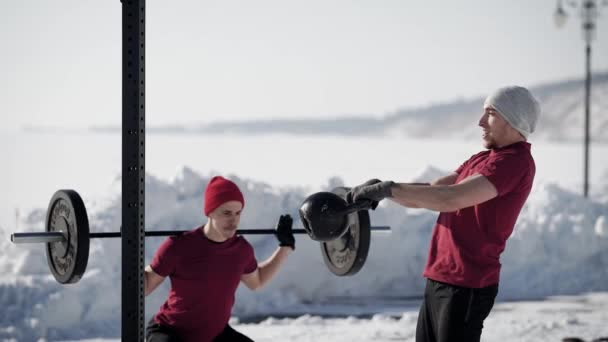 Two athletic crossfit sportsmen training on the nature in winter.
