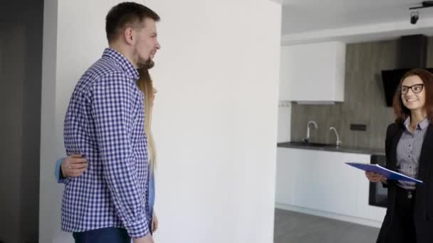 real estate agent woman is showing new flat to young married pair, entering in a living room with kitchen