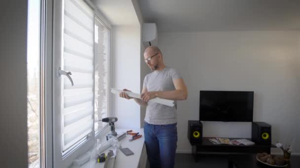 mistr je instalace bílé Plastové okenní rolety ve světlé místnosti v průběhu dne, měření a vyzkoušení na plátně