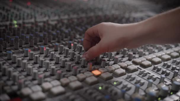 Musician is working in a recording studio with a mixing console.