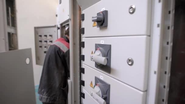 un elettricista professionista lavora con una protezione elettrica, un uomo ripara luce ed elettricità in un condominio