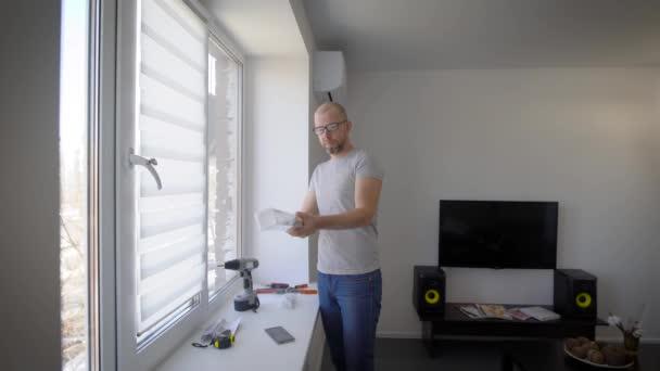 dospělý muž rozbalí obalu od záclony, visí lidi na okno se sluneční clonou v obývacím pokoji