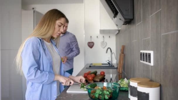 Krásná blondýnka je sekání zeleniny stojí v moderní kuchyni