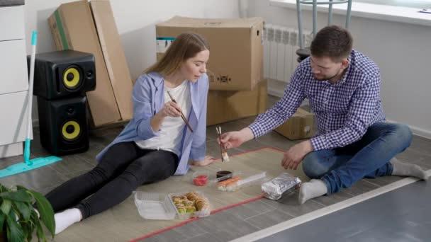 Mladý muž a žena slaví pohybují a jíst sushi, zatímco sedí na podlaze