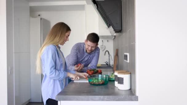 Boční pohled na mladý pár stál dohromady a vaření zeleniny na kuchyň v bytě