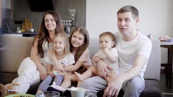 šťastný rodinný pár s tři malé dcery jsou na gauči v obývacím pokoji a sledování televize v denní
