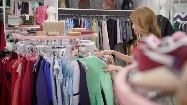 ebfc5dbcd Garota sozinha comprador está passeando na área de vendas na loja de moda  com roupas femininas