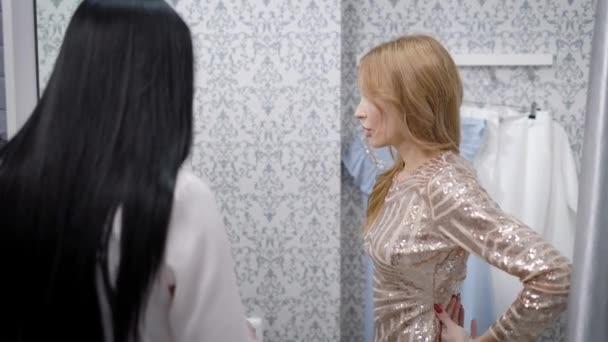 blond dívka se snaží lesklé šaty v šatna, při pohledu do zrcadla a radí se svým přítelem, bruneta