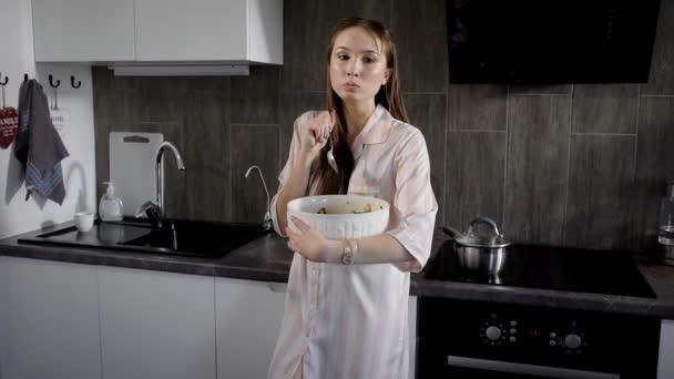 Mladá bruneta žena je jíst salát z velké mísy v kuchyni nošení pyžama