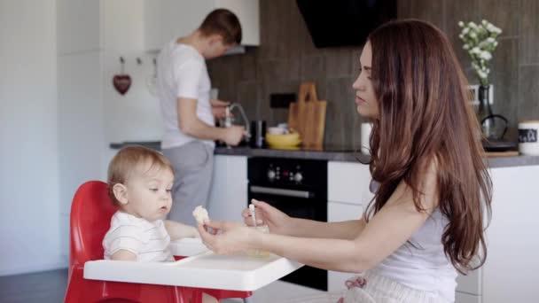 Okouzlující účetní brunetter matka je krmení její krásné malé dítě