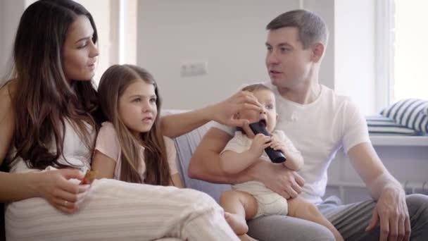 Evropská rodina sedí na gauči u televize.