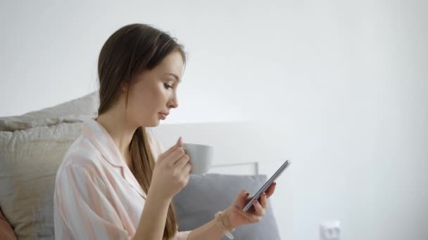 portrait of a pretty woman who holds a cup and a smartphone in her hand, a lady watches news on a gadget and drinks tea