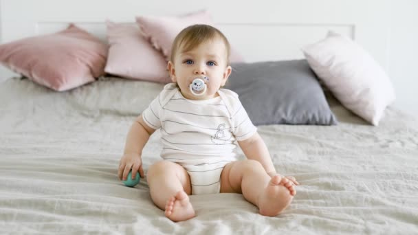 a cute and funny child sits on a bed with a pacifier in his mouth and balls in his hand, the boy looks ahead
