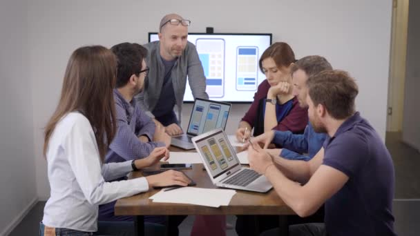 Creative business. A team of developers and designers discussing the layout of a mobile application. Men and women in casual clothes.