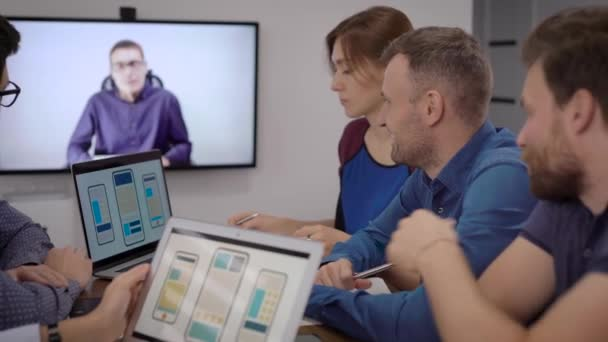 Software-Entwickler für Mobiltelefone hören Chef-Spezialist per Videoanruf im Konferenzraum zu