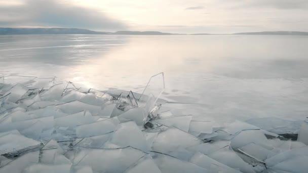die nördliche Landschaft eines gefrorenen Sees oder Flusses. Eissplitter in Küstennähe, in der Ferne Berge und Horizont.