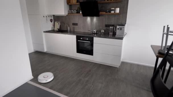 Ve stylové moderní kuchyni je úklid. Automatický robotický vysavač se pohybuje po trajektorii. Prvky chytrého domova usnadňují život lidem