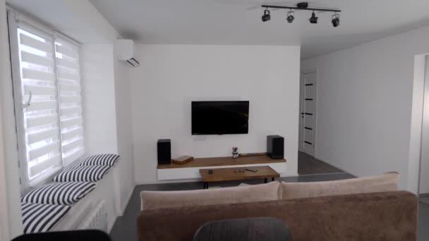 Prostorný světlý obývací pokoj v moderních apartmánech. Čisté, minimalistické bydlení ve skandinávském stylu. Návrh interiéru