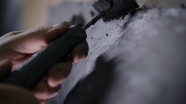 A close-up of a mans hand with a tool. A professional removes the form from the clay with the help of a cycle. The production