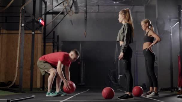 Zwei Sportlerinnen wiederholen Übungen mit Medizinball in Turnhalle beim Krafttraining mit Trainer