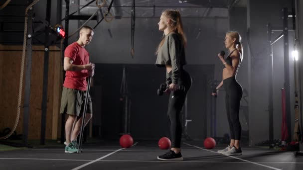 zwei Athletinnen trainieren mit Kurzhanteln im Fitnessclub, Personal Workout mit Trainer