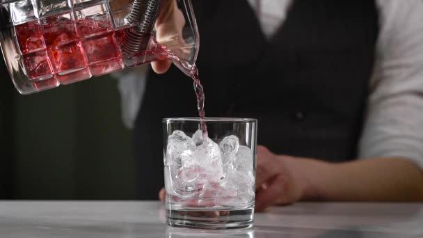 Detailní záběr v nočním baru. Barman nalije dopitý koktejl do sklenice. Krásná nabídka nápojů je v průmyslu důležitá.