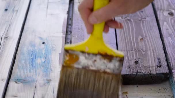 A keretben van egy nagy ecset és barna festék a fán. A régi falitábla díszítése.