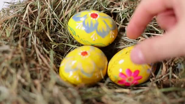 A hand cvollects a few easter eggs from a pile of straw.