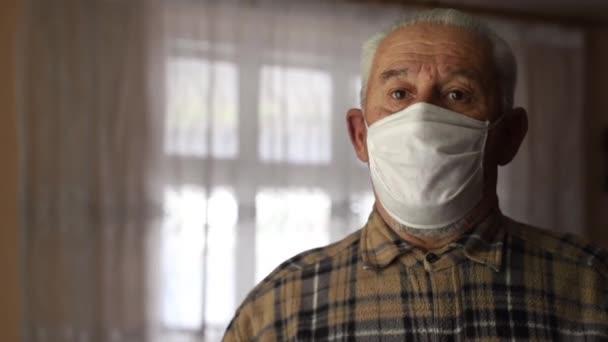 Idősebb férfi, nehezen lélegzik maszkban otthon. A koronavírus pamdemiája