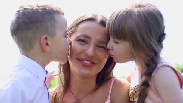 Glückliche junge Mutter mit Tochter und Sohn auf der grünen Wiese