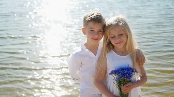 Geschwister am Teich an einem sonnigen Tag, glückliche Kinder, Sommerferien für Kinder, Kinder haben Spaß am Fluss