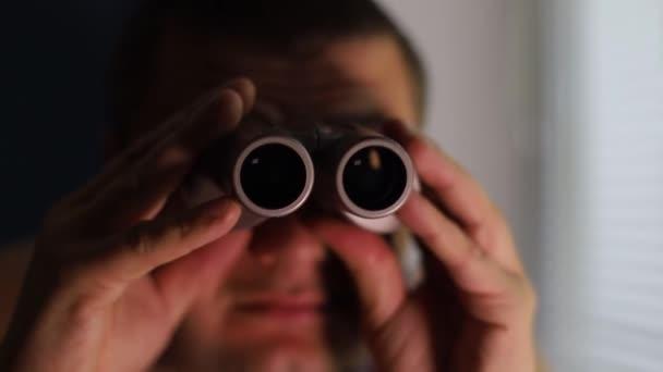 Az az ember kémkedik az emberek után, távcsövet használ.