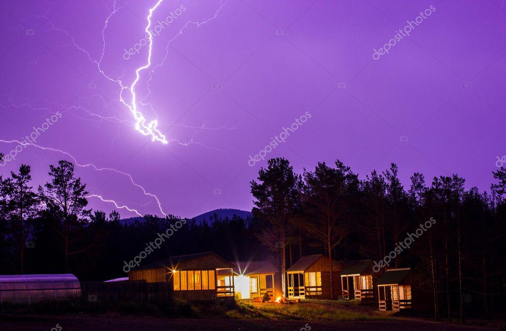 Lightning in the night sky over houses