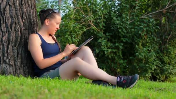 Fiatal nő ül egy zöld fű alatt fa a parkban használja Tablet Pc