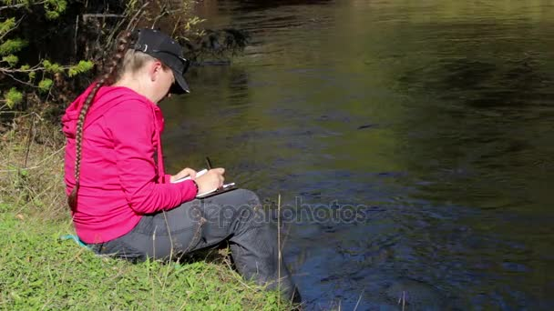 Girl in pink hoodie makes notes in a notebook sitting by the river. With sound