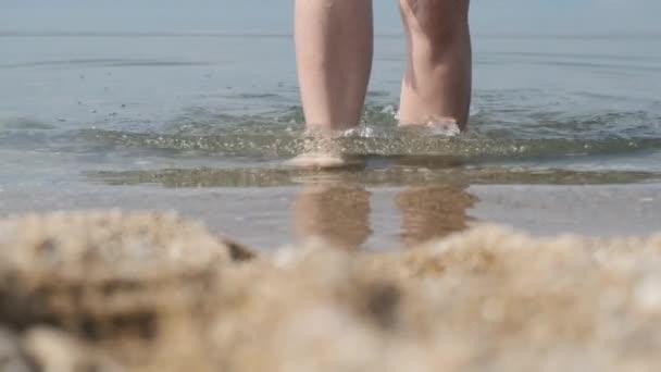 Detailní záběr ženských nohou na pláži, vycházejících z vody