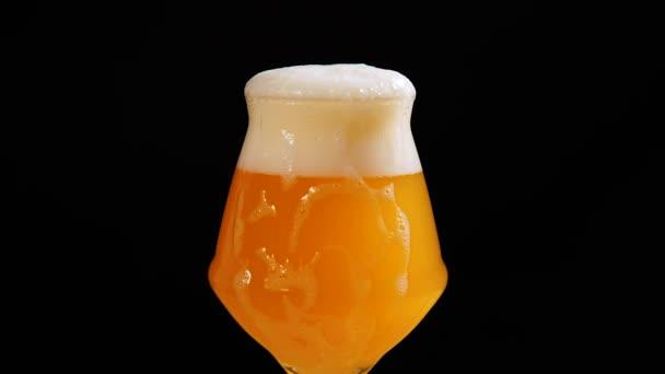 Světlé pivo se sype do skla. Ze skla kapala pěna. Studené pivo ve sklenici s kapkami vody