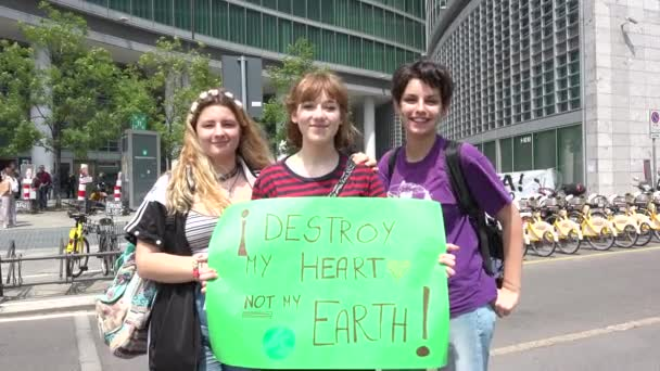 MILAN, ITALY - MAY 24, 2019 Happy girls demonstrating at global strike for climate. Students skipping school with green picket signs, smiling young women at Friday for future event, ecologist movement