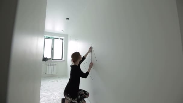 The girl draws a geometrical figure in the room